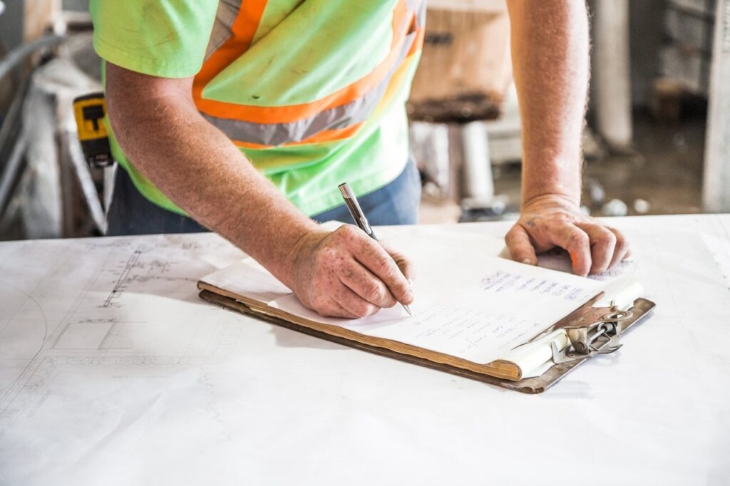 construction person writing on a clip board