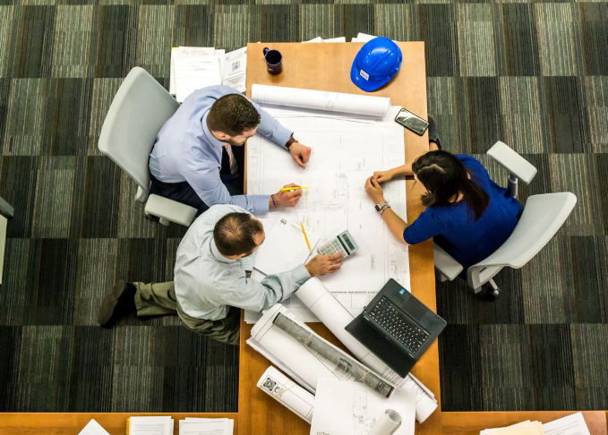 colarelli construction team at an office table looking over building plans