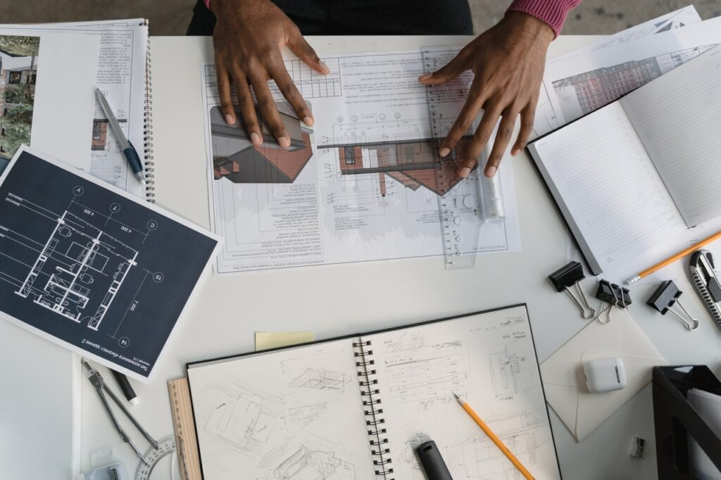 desk flatlay with architecture and construction sketches and person's hands
